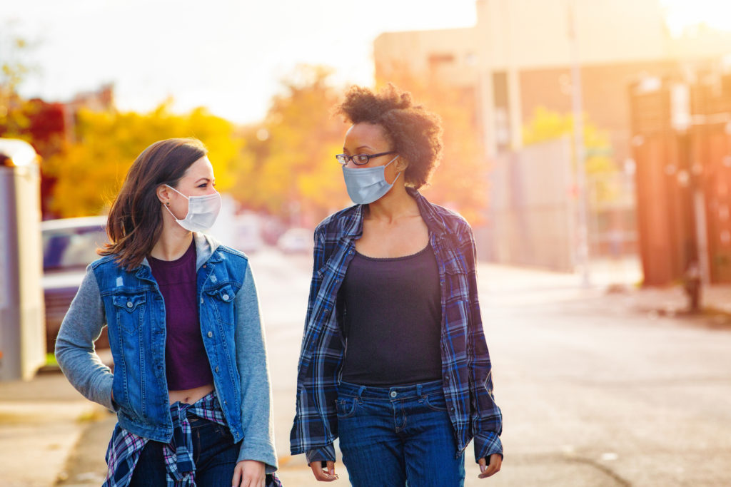 Two female friends walking down a Brooklyn alley wearing face masks