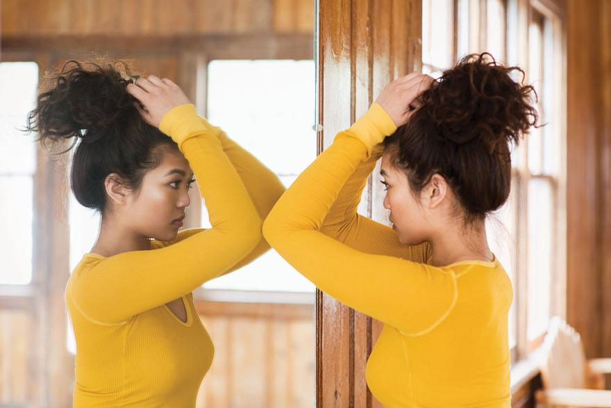 girl looking in the mirror for new changing unusual moles